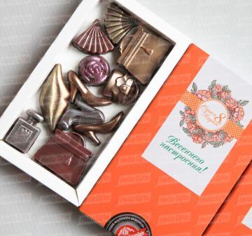 Клиентам и коллега подарки на 8 марта 2017  шоколадки в виде дамских аксессуаров – 11 предметов: большие сумочки - 2 шт., маленькая сумочка, веер – 2 шт., флакончик духов, туфельки - 3 шт., губы и розочка с колорированием (пищевойкраситель). Картонная упаковка, шубер из дизайнерской бумаги, брендирование в виде наклейки с логотипом компании, при больших тиражах возможна полноцветная печать шубера. Любые варианты индивидуального оформления и персонализации: тиснение, УФ лакировка и т.п. Подарок можно дополни