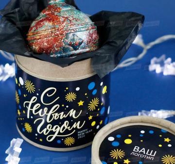 Новогодний ёлочный шар из темного шоколада  Корпоративные подарки на Новый год 2020 оптом Итальянский тёмный шоколад, содержание какао 54%. Вес: 140-150 г, диаметр 10 см. Шар внутри полый. Возможно изготовление шоколадных шаров с начинкой. Упаковка: картонный тубус (брендирование бесплатно). Размер: диаметр 12,2 см, высота 15 см. Вес подарка: 260 г. Изготовим индивидуальные новогодние ёлочные шары из шоколада с барельефом в тематике мероприятия, логотипом вашей компании.