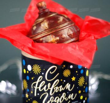 Итальянский тёмный шоколад, содержание какао 54%. Вес: 140-150 г, диаметр 10 см. Шар внутри полый. Возможно изготовление шоколадных шаров с начинкой. Упаковка: картонный тубус (брендирование бесплатно). Размер: диаметр 12,2 см, высота 15 см. Вес подарка: 260 г. Изготовим индивидуальные новогодние ёлочные шары из шоколада с барельефом в тематике мероприятия, логотипом вашей компании.  Новогодний ёлочный шар из темного шоколада  Корпоративные подарки на Новый год 2020 оптом