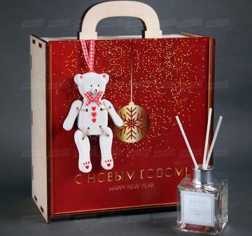 Полезные Новогодние подарки оптом | - Вино красное 250 мл - Бокал для глинтвейна - Специи для глинтвейна в мешочке 30 г - Рецепт приготовления глинтвейна - Ёлочная игрушка «Мишка», дерево 14 см - Ароматический диффузор для дома «Christmas tree» 90 мл - Марципановая буханка Zentis Marzipan 100 г - Упаковка: чемоданчик из дерева с полноцветной печатью, брендирование бесплатно