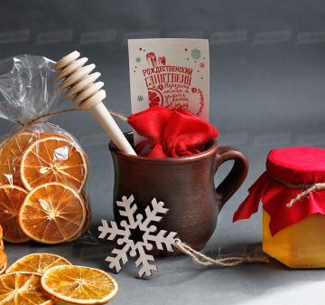 Съедобные корпоративные новогодние подарки | - Кружка глиняная 0,3 л - Набор конфет ручной работы 6 шт. - Мёд в стеклянной баночке 200 мл. - Ложка для меда - Сушеный апельсин, 30 г (cушка при t 36 градусов, сохранены все витамины и полезные свойства фрукта) - Специи для глинтвейна в мешочке 30 г - Рецепт приготовления глинтвейна - Деревянная новогодняя ёлочная игрушка 1 шт. - Крафт коробка с брендированым шубером. Размер: 22x21x11 см. Вес подарка: 1600 г.