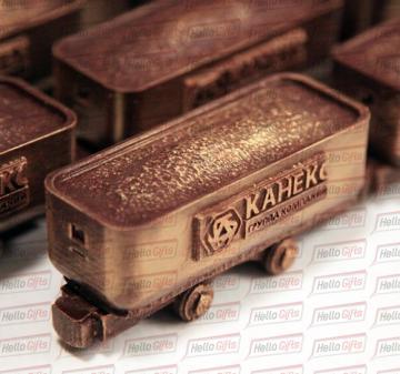 Механизмы и техника  из шоколада/ Подарки машиностроителям к Новому году и профессиональным праздникам |   Шоколадная фигура «Вагонетка с логотипом компании» Габариты шоколадной фигуры Вагонетка 110 х 45 х 50 мм., вес 160-170 гр.  Бельгийский темный шоколад Barry Callebaut,  54%.  Упаковка: подарочный пенал из дерева с полноцветной прямой печатью (брендирование).  Размер упаковки: 140 х 65 х 80 мм.